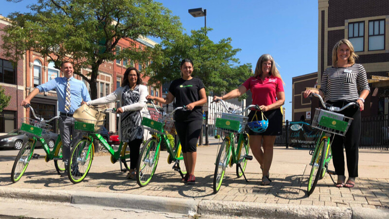 5 people holding Lime bikes in Green Bay