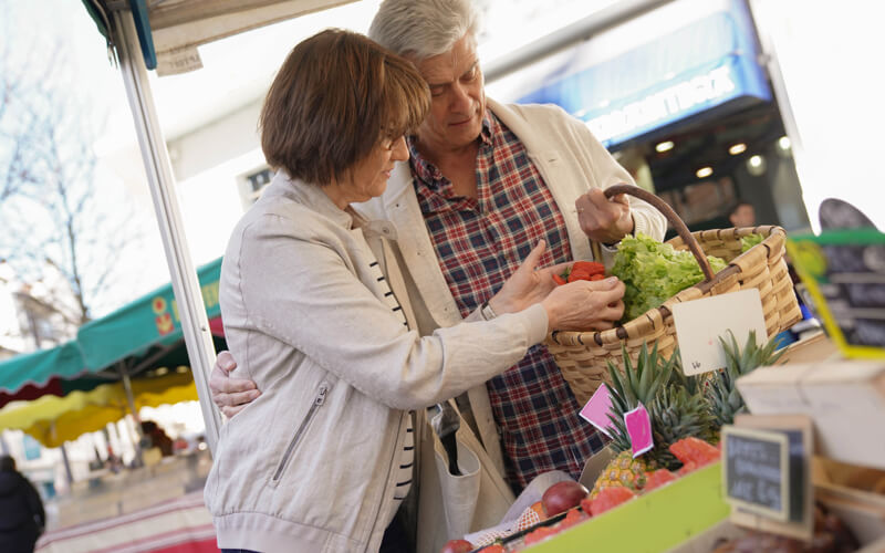 senior couple shopping for produce at a farmers market