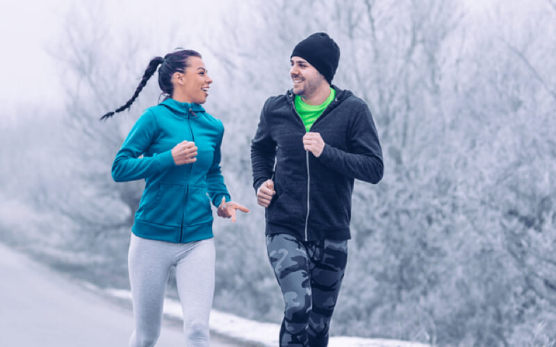 woman and man running on a snowy trail in the winter