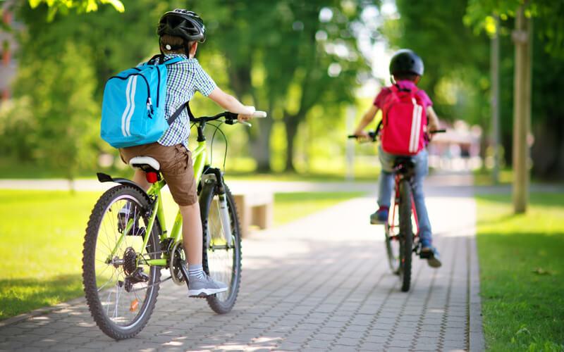 two kids biking on trail