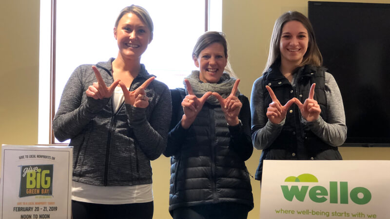 "3 women showing 'w' with hands to show ""Wello"""