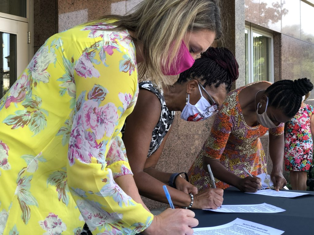 (From left to right) Natalie Bomstad of Wello, Robyn Davis of Brown County United Way and Renita Robinson of YWCA sign on to the declaration.