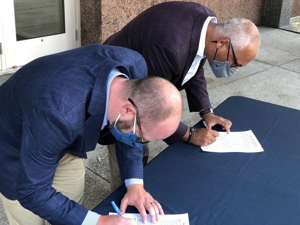 (From left to right) Mayor Eric Genrich of the City of Green Bay and Dr. Ashok Rai of Prevea Health sign on to the declaration.